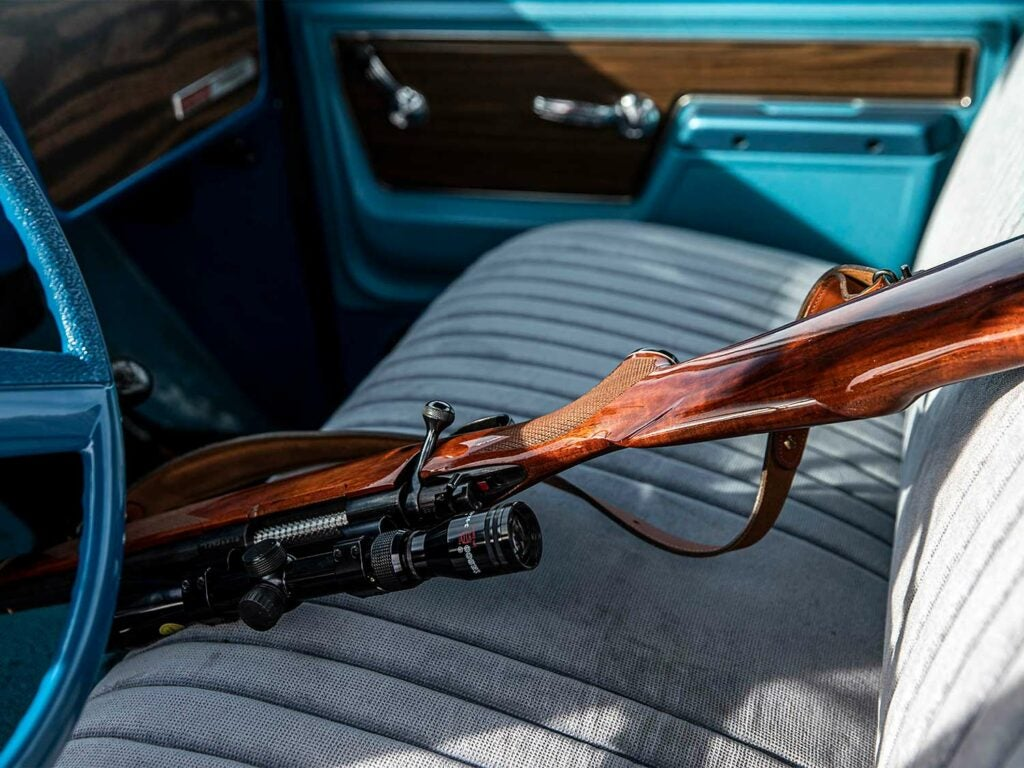 A hunting rifle is placed in the seat of a truck.