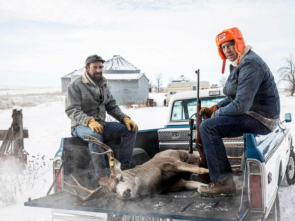 Two hunters sit and pose in the bed of a truck next to a mule deer.