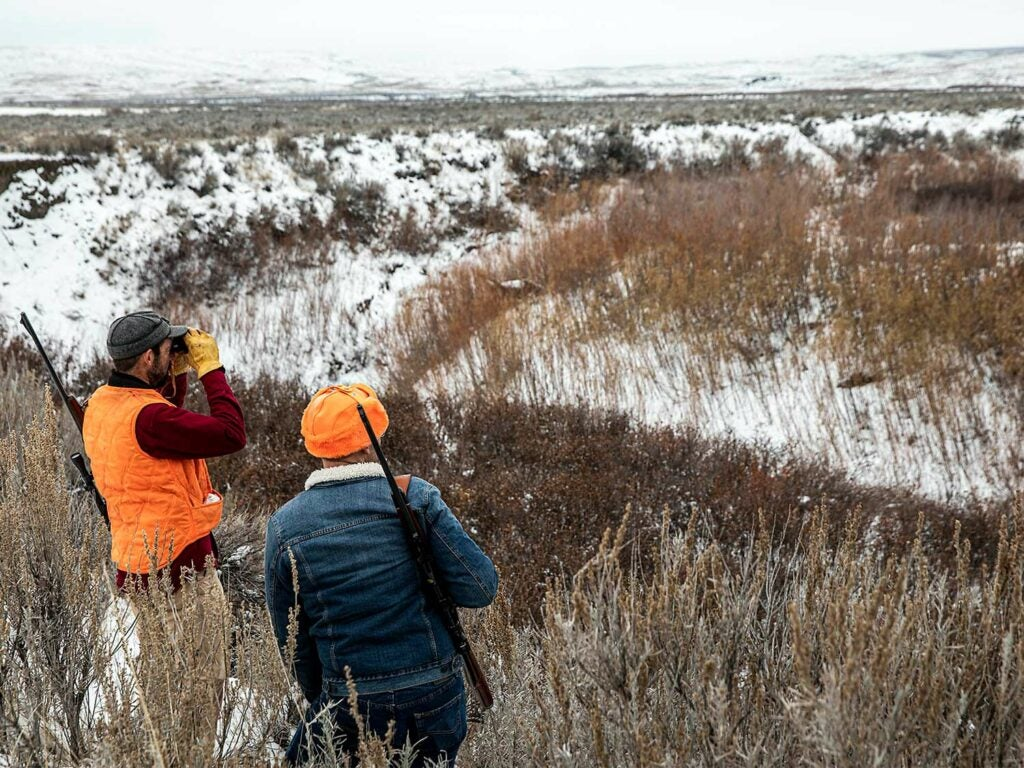 Two hunters scout an open, snow covered plain.