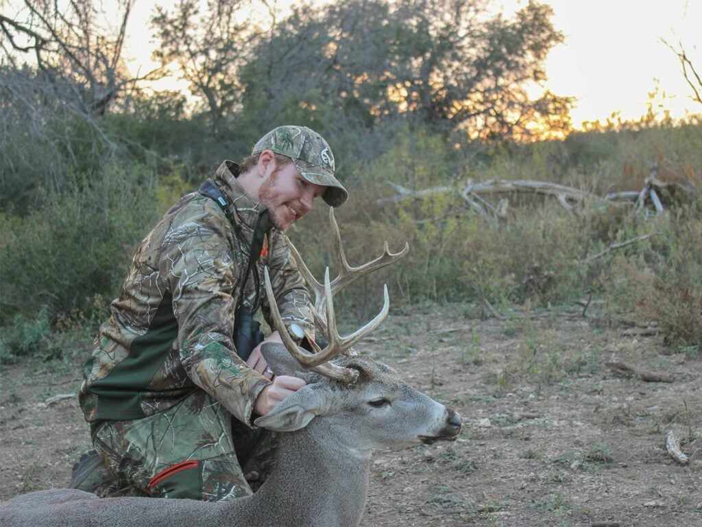 A hunter kneeling next to a whitetail buck.