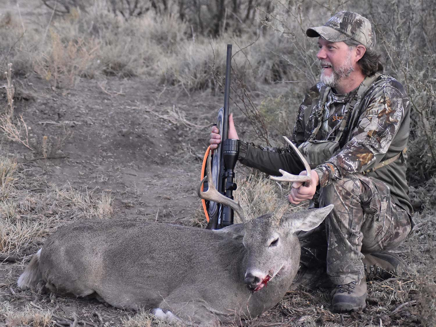A hunter kneels next to a whitetail buck.