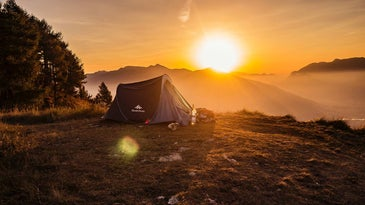 A camping tent on a hillside overlooking mountains and a sunset.