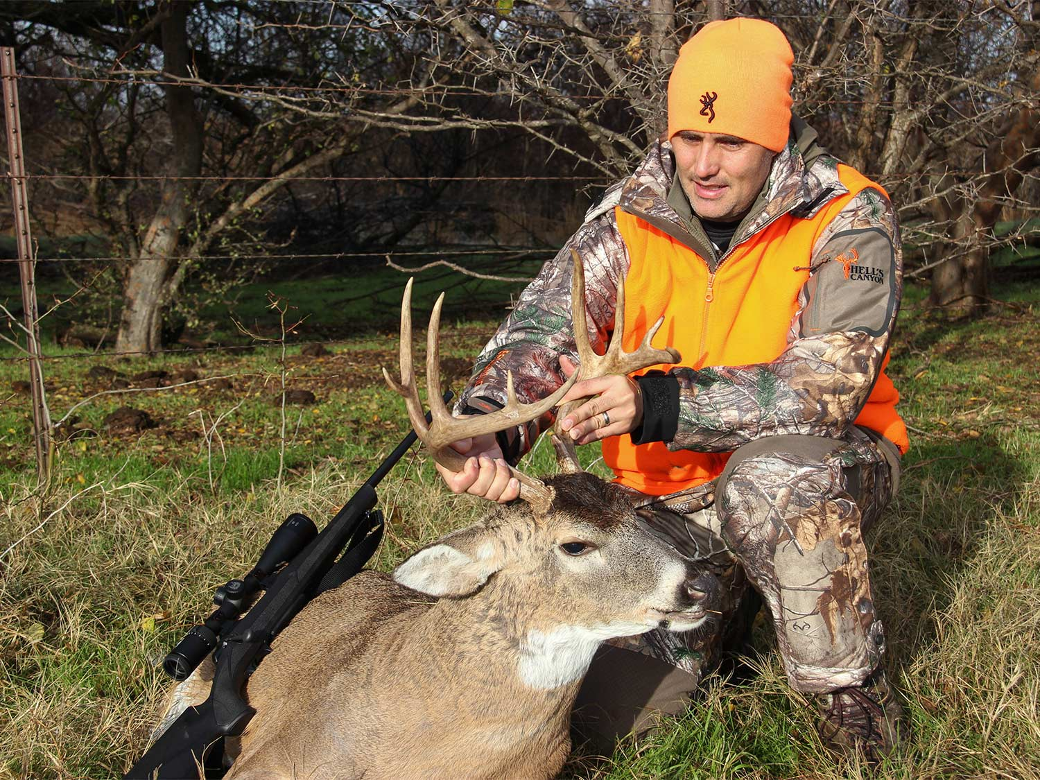 A hunter in camo and orange kneels next to a whitetail buck.