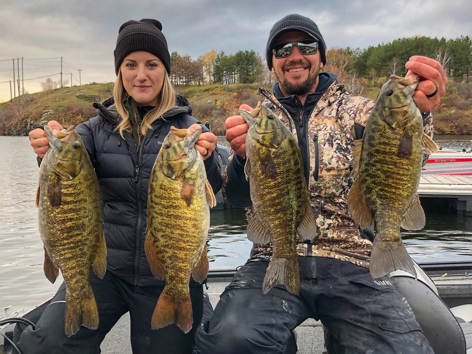 Two anglers hold up four smallmouth bass.