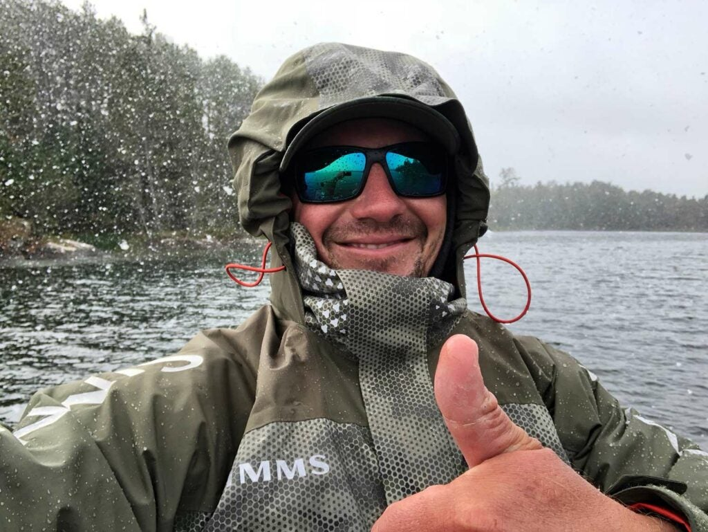 An angler smiles and thumbs up at the camera in the snow.