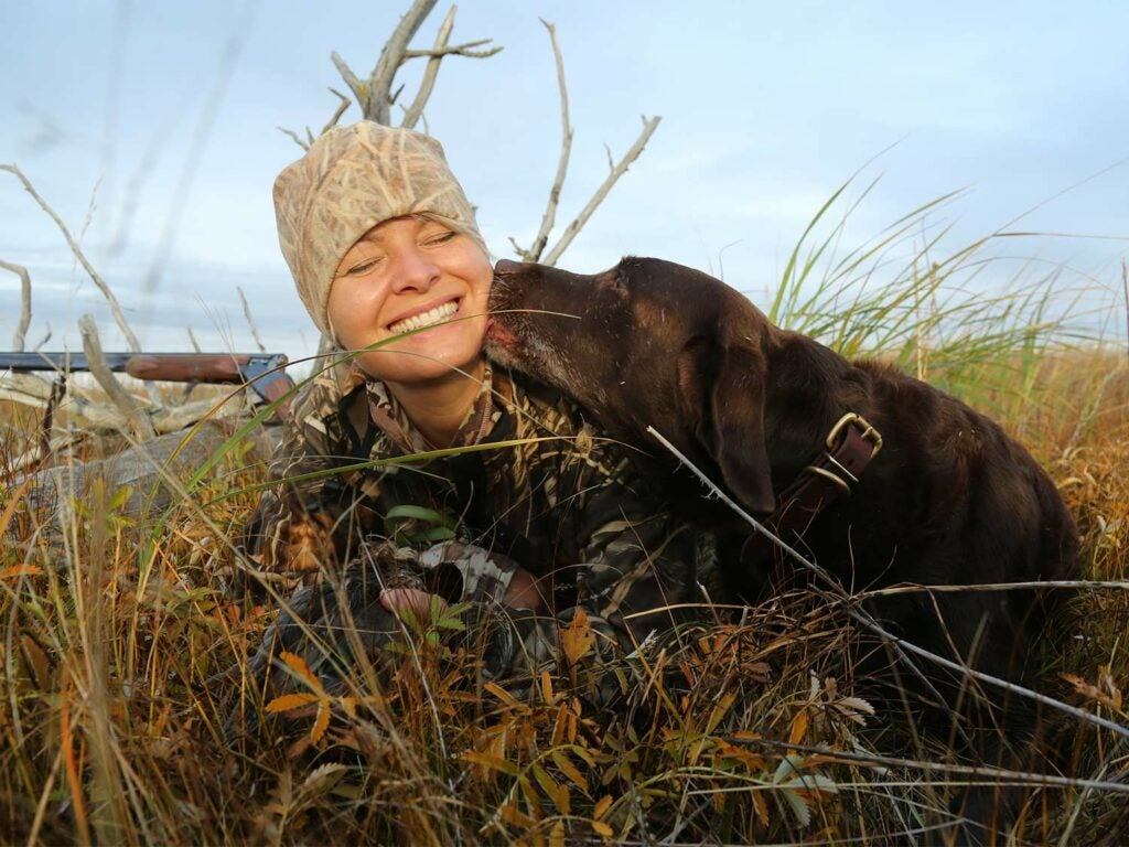 A woman in full hunters camo sits in a field while a chocolate lab licks her face.