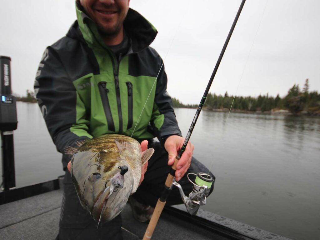 An angler holds up a bass.