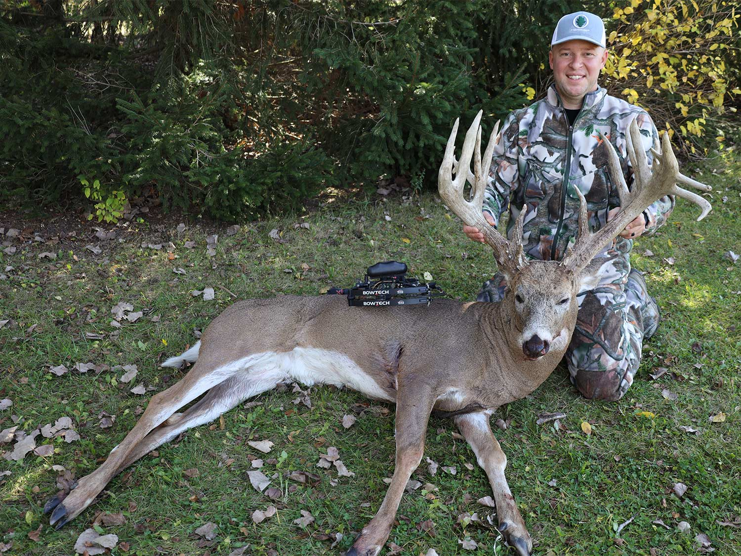 A hunter kneels behind a whitetail buck and hold its head up by the antlers.