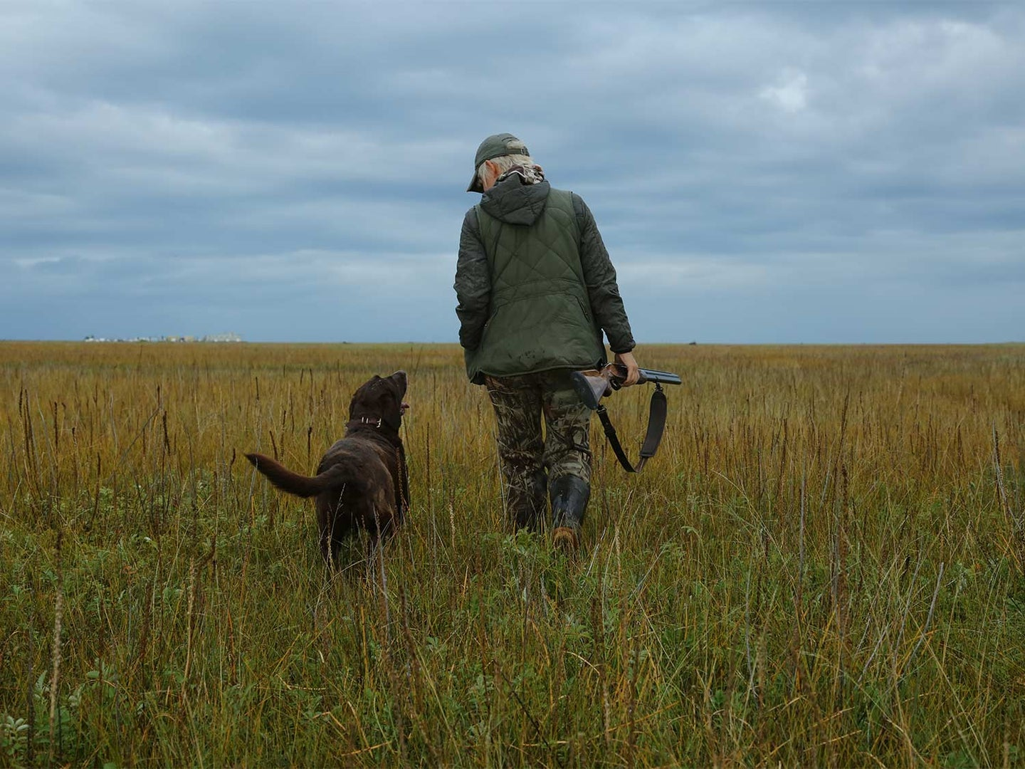 A hunter in camo and jacket holds a gun while walking through an open field. A hunting dog walks beside them.