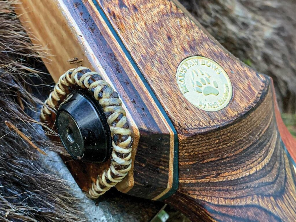 Close up detail of a metal medallion inset into the wood of a traditional longbow