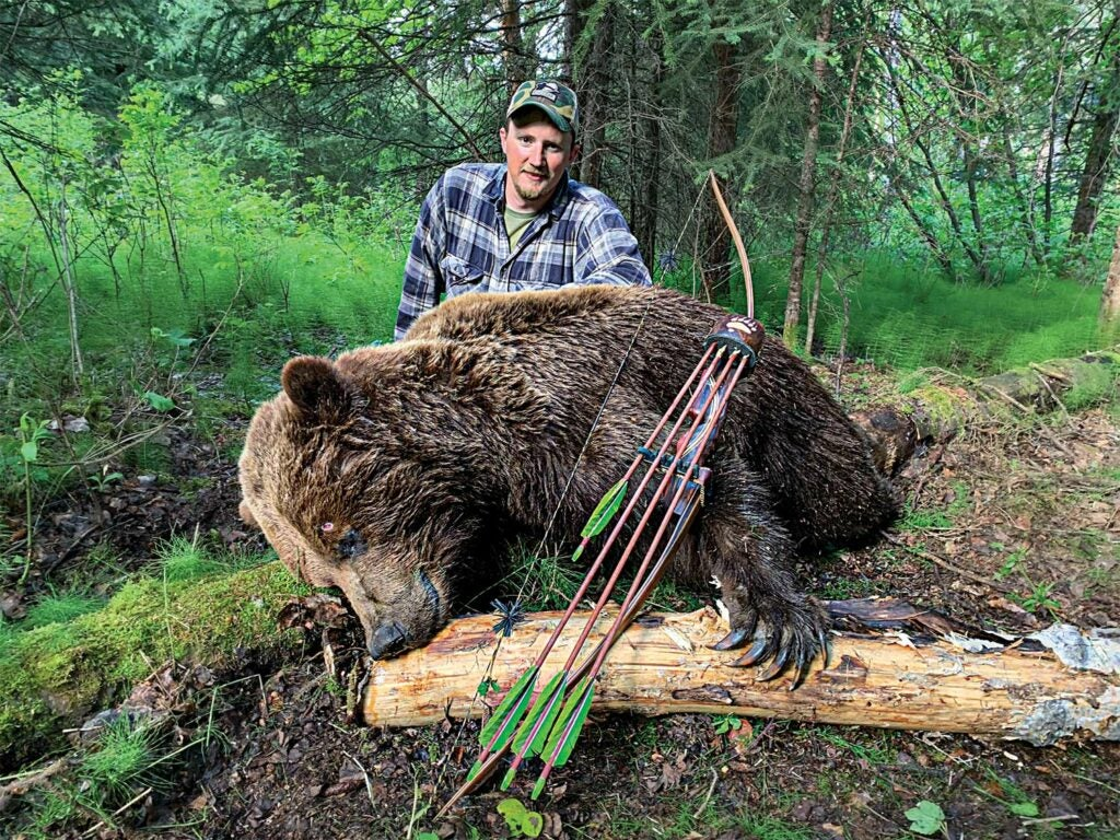 A hunter poses behind a dead grizzly bear with a bow and arrow set laying against it.