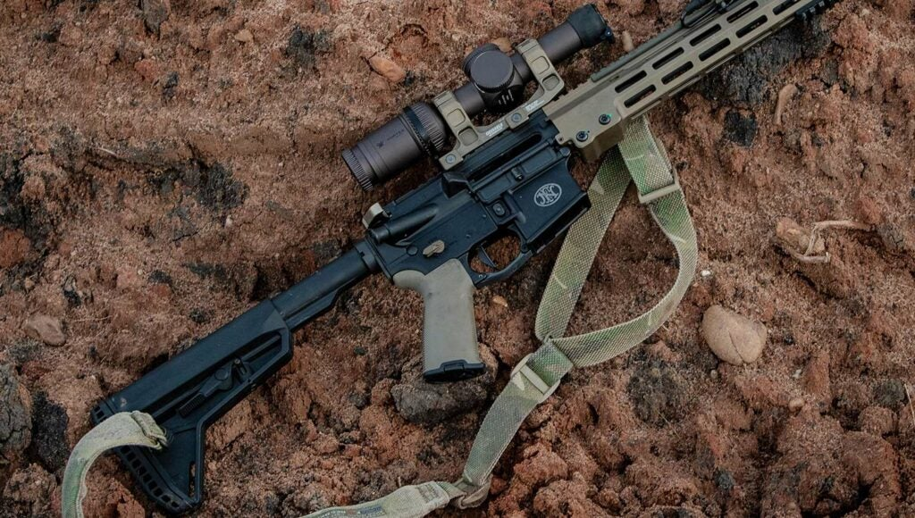 An AR rifle laying on the rocky ground.