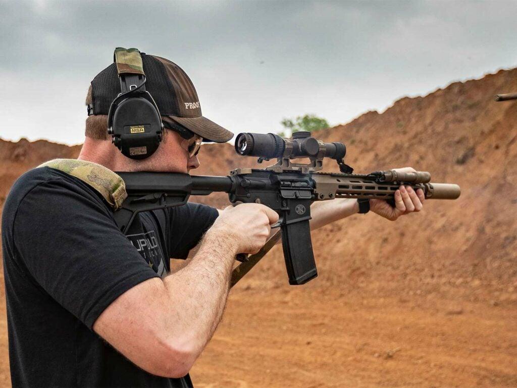 A man aims a rifle at a shooting range.