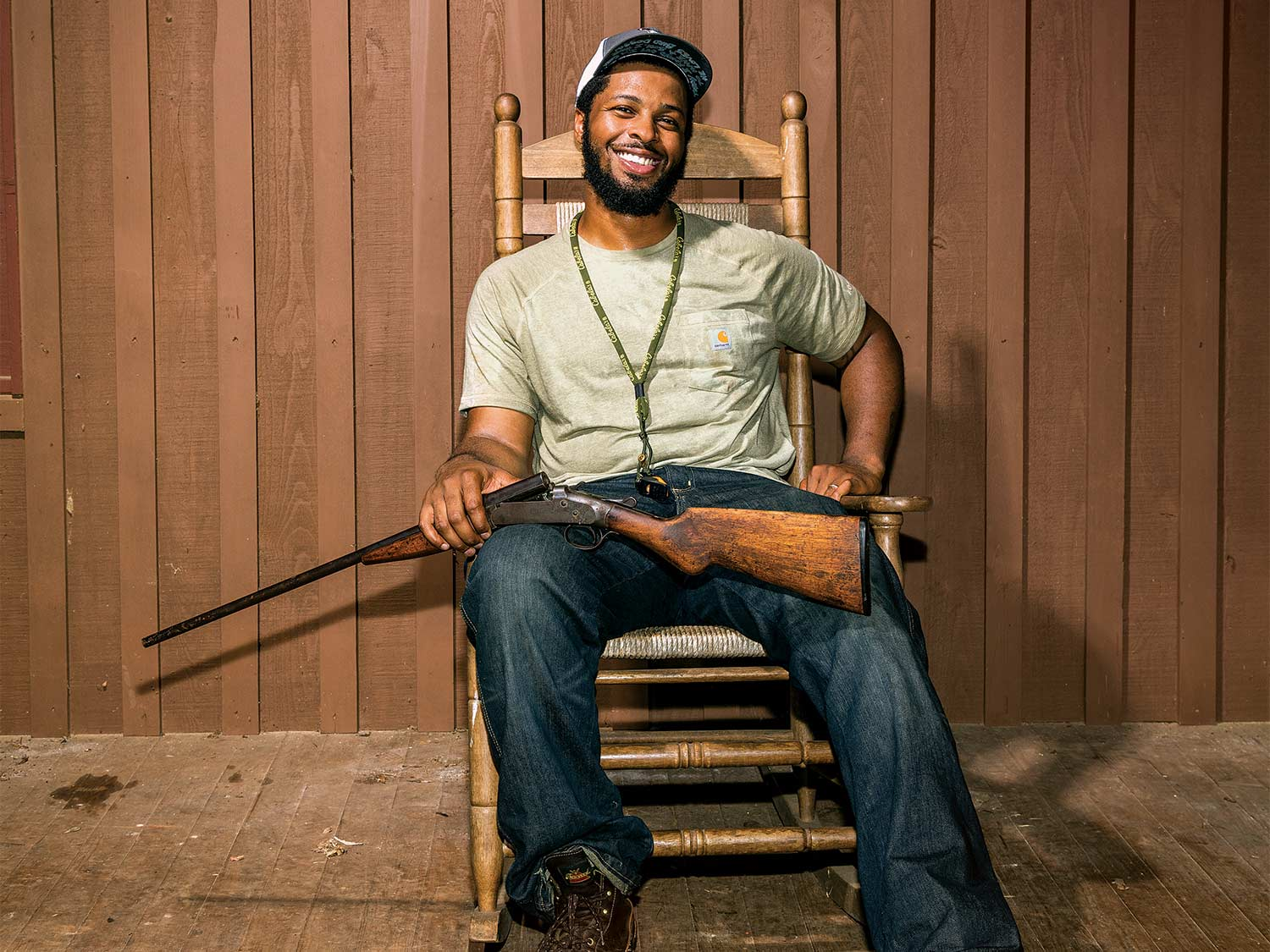 A hunter sits in a rocking chair, smiling, with a gun in his lap.