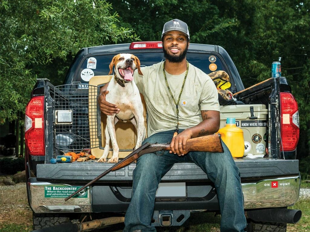 A hunter smiles, seated on a truck tailgate, with his hand wrapped around his dog.