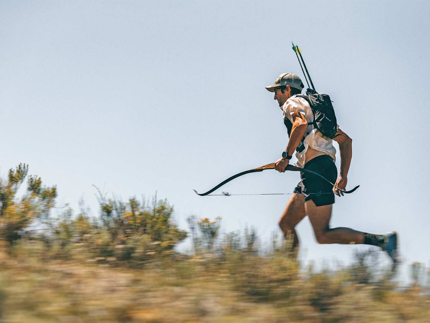 A hunter holds a traditional bow and runs through an open field.