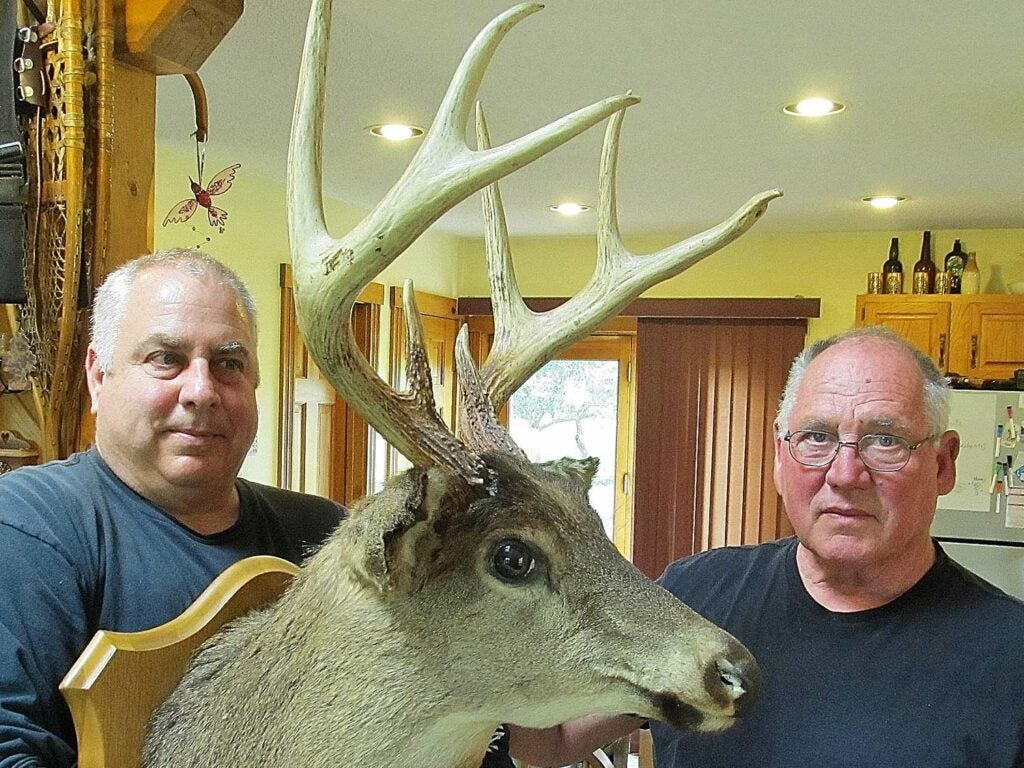 Two men hold up a large trophy buck mount.