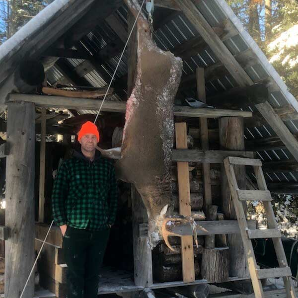 A hunter stands next to a buck hanging from a hunting camp hook.