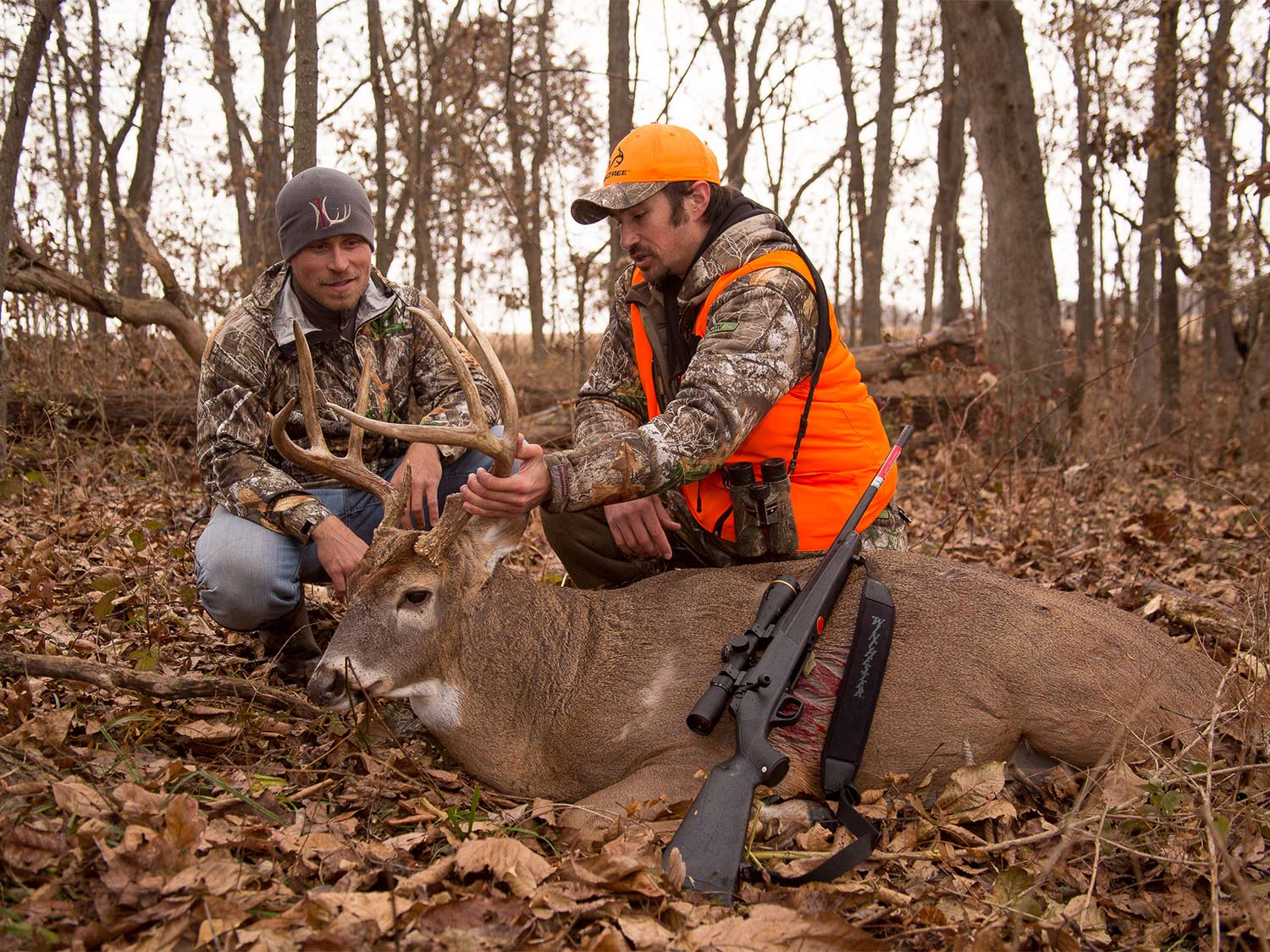 Two hunters kneel behind a deer and hold its head up by the antlers.