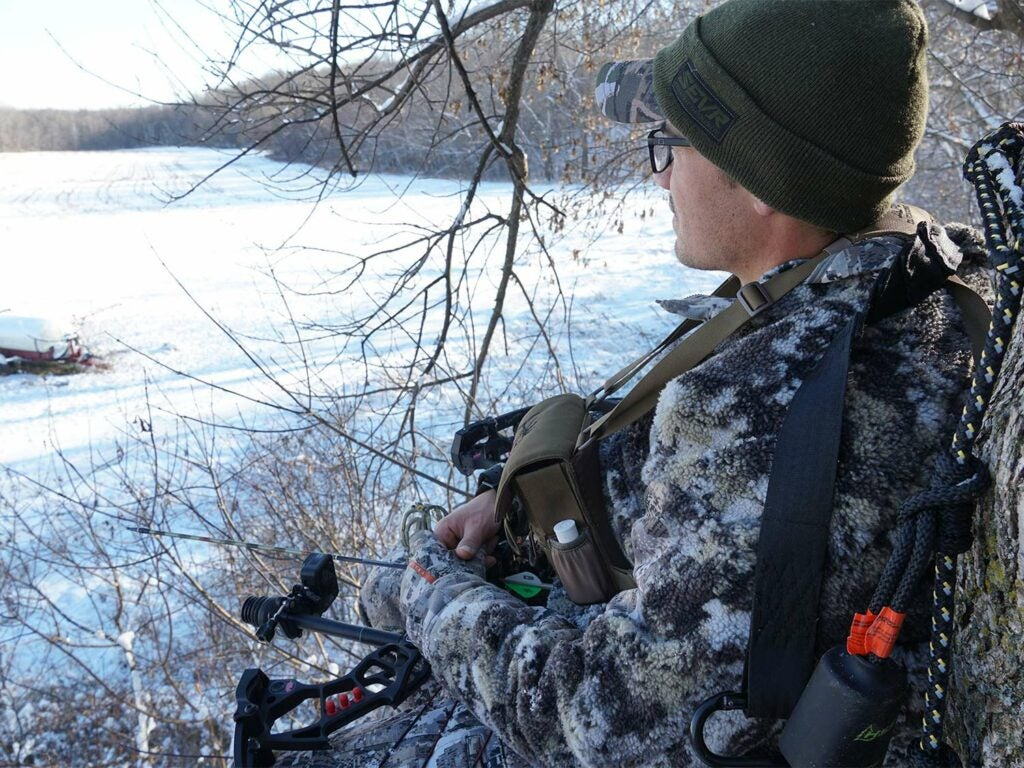 A hunter in full camo looks out over a field covered in snow.