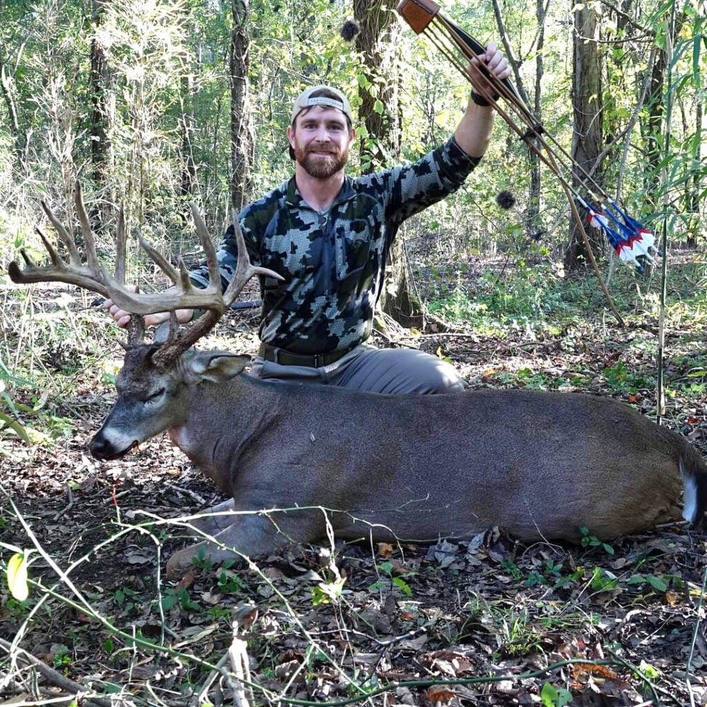 A hunter holds his bow aloft beside a giant whitetail buck in the woods.