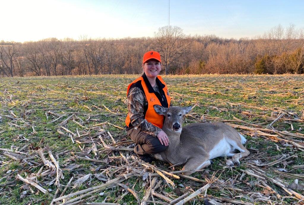 A female hunter in blaze orange kneels beside a doe in a cut cornfield in early winter.