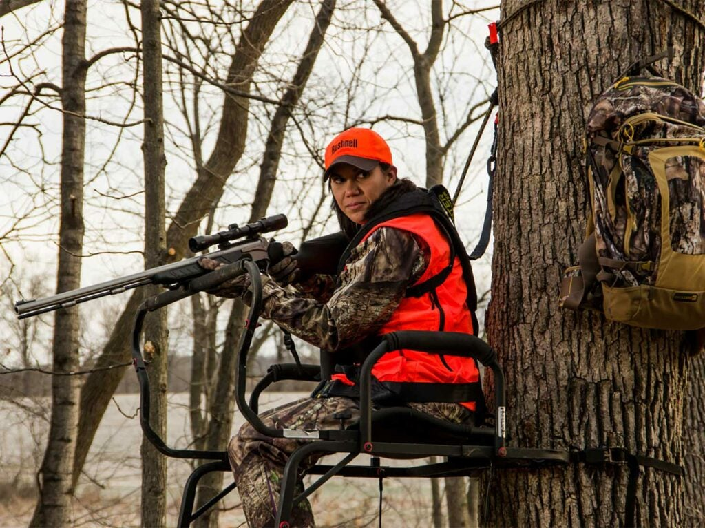 A woman hunter in full camo and an orange vest holds a scoped rifle while seated in a tree stand.