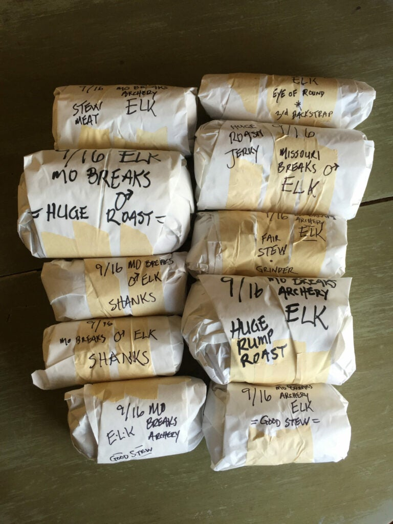 Wrapped packages of elk venison on a table, wrapped in butcher paper and venison with writing on them.
