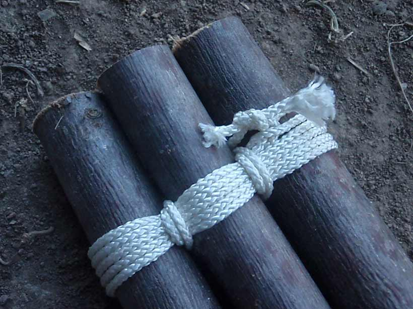 Three logs tied together with lengths of rope.