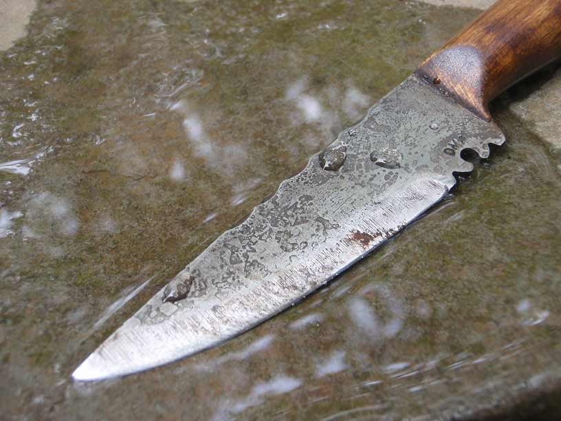 knife being sharpened against a smooth, wet rock.