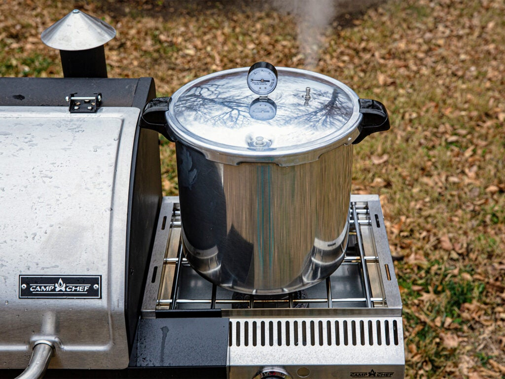 A pressure canner on the side of a camp chef grill.