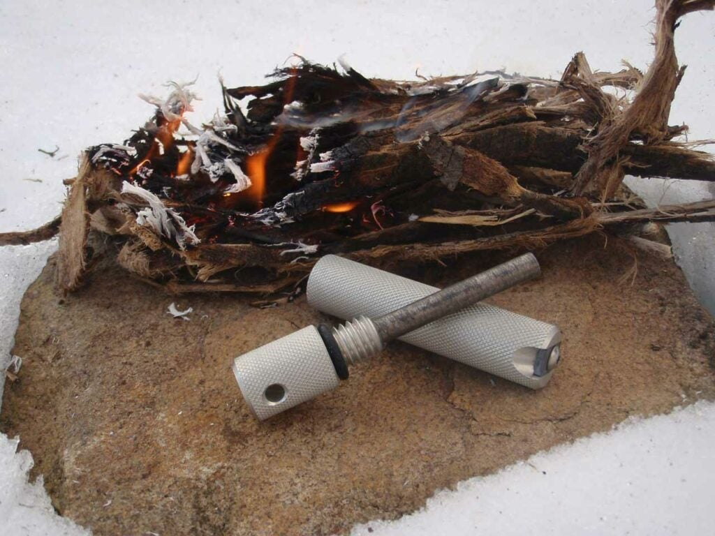A small fire burning in tinder next to a large fero rod.