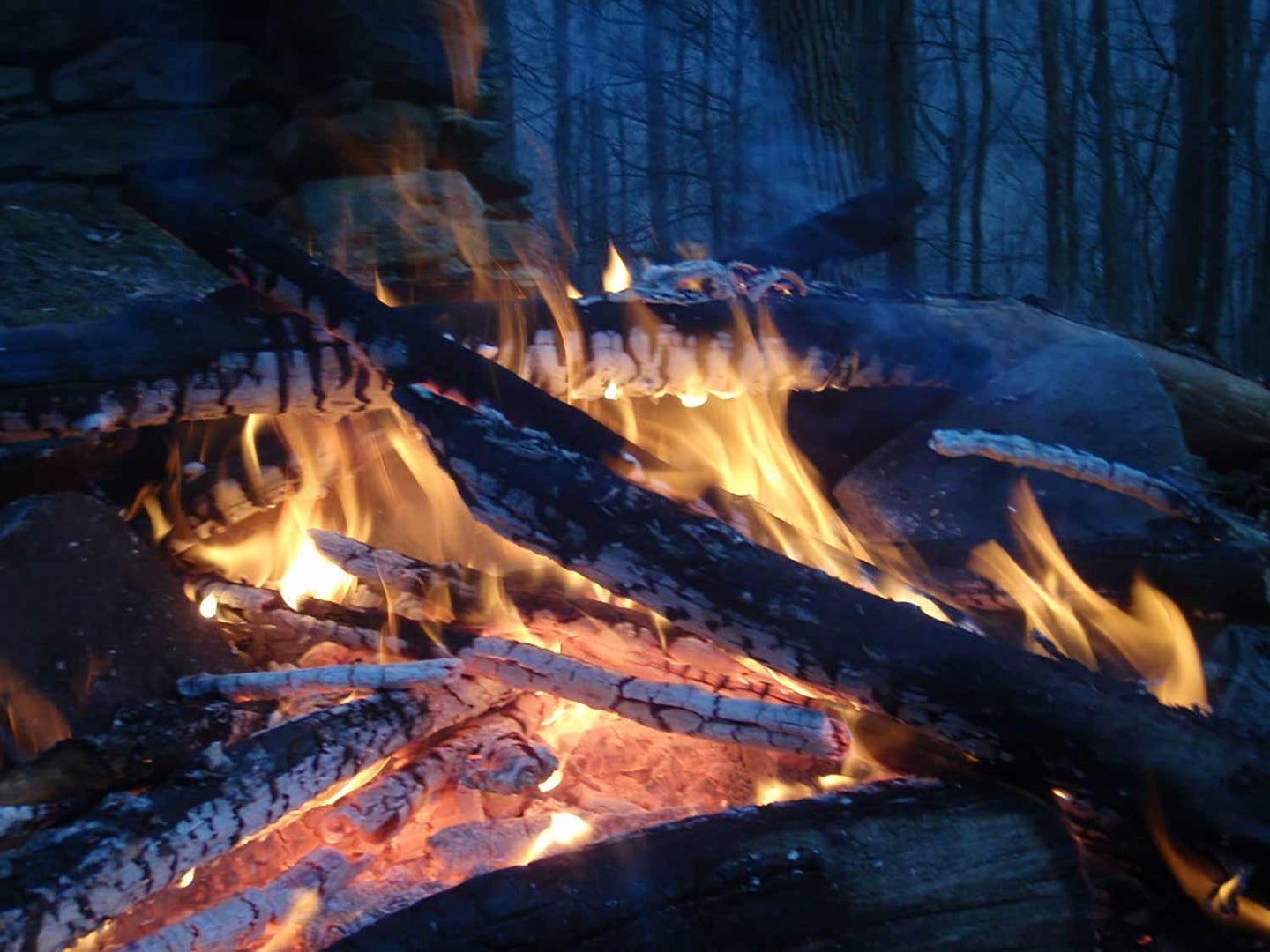 Piles of wood burning and turning to charcoal during a nighttime campfire.