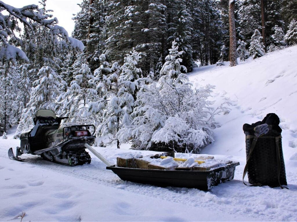 A snowmobile attached to a hunting sled and gear.
