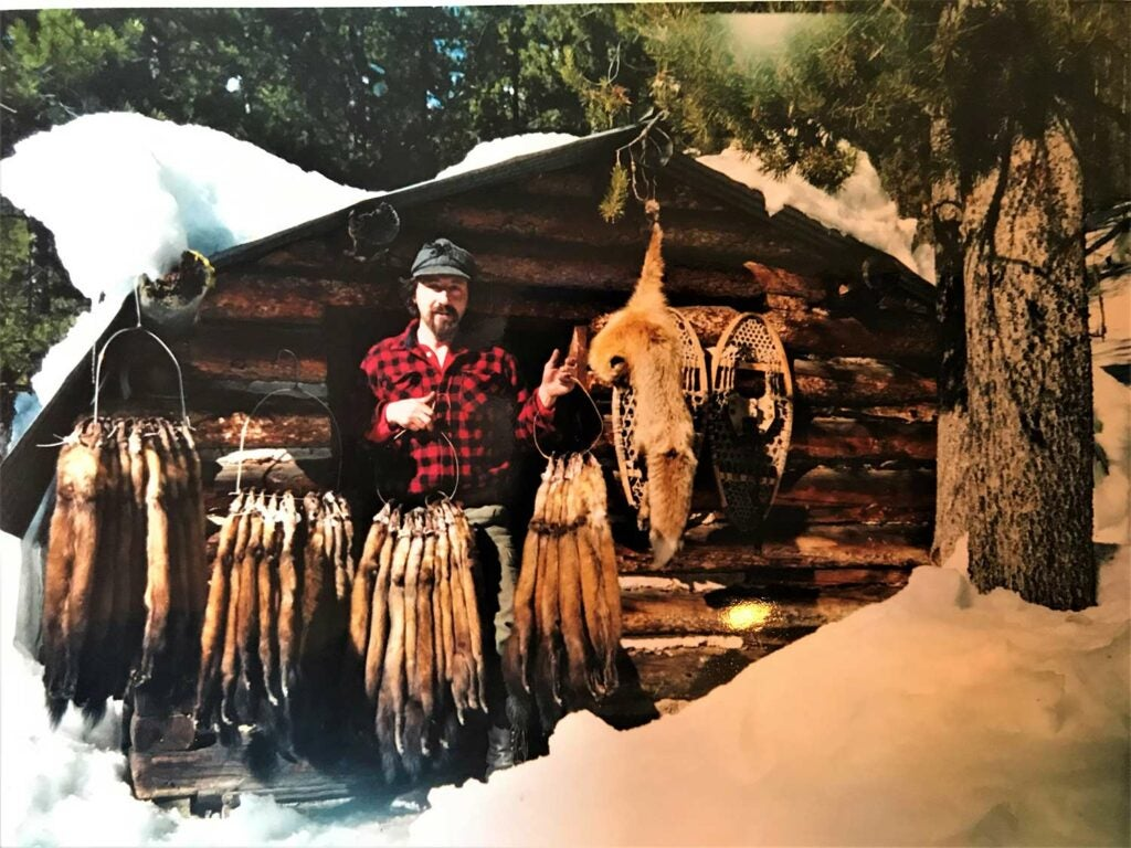 A hunter next to a cabin covered with marten furs.