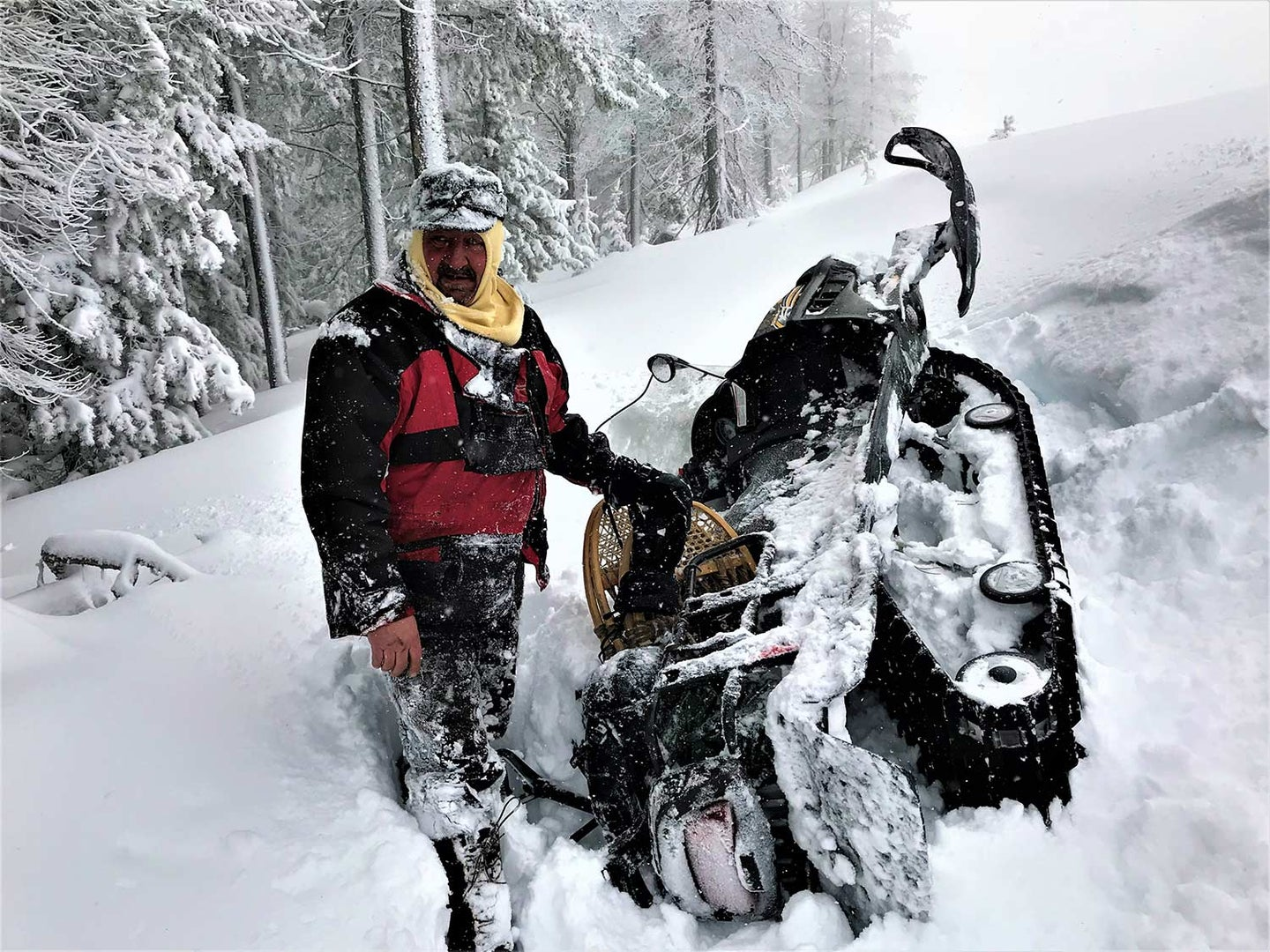 A hunter kneels in the snow next to an overturned snowmobile.