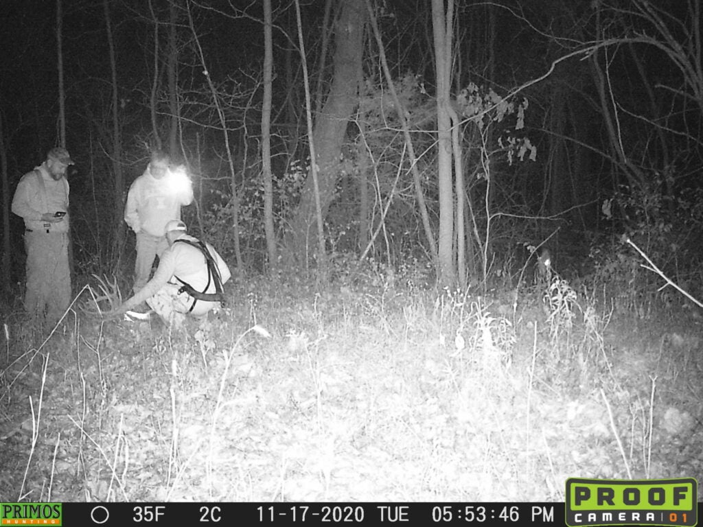 Three guys gathered around a big whitetail buck, on a black and white trail cam photo.