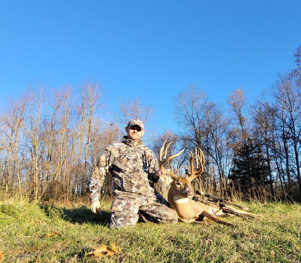 A hunter kneeling in the grass beside a giant double-main-beam buck.