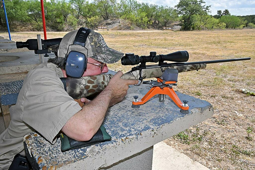 A hunter aims a scoped rifle at a shooting range.