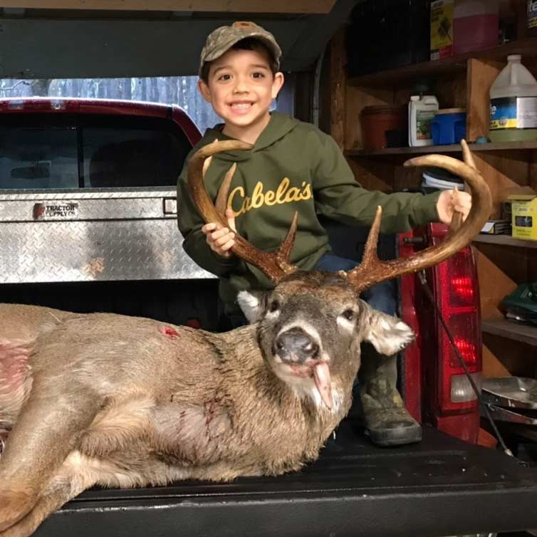 A whitetail buck on a tailgate. A young boy stands next to it.