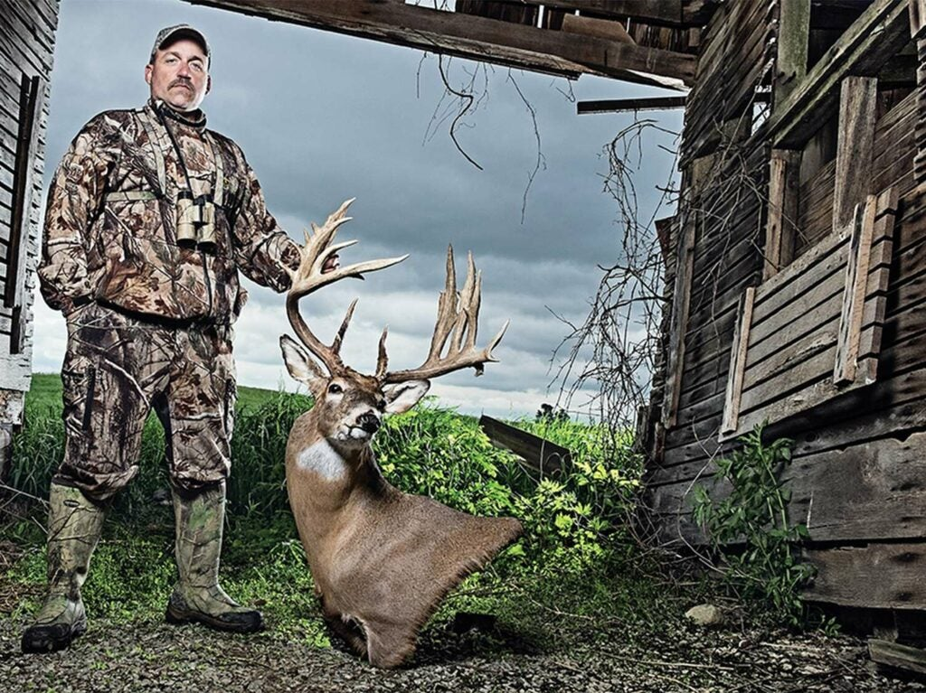 A hunter holds a whitetail deer trophy.