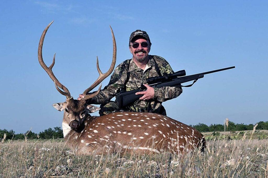 A hunter kneels next to a axis deer.