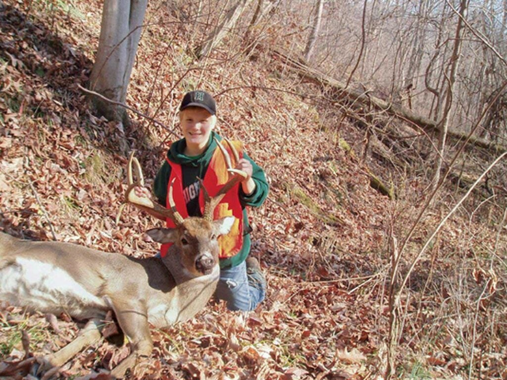 A hunter kneels next to the whitetail deer.