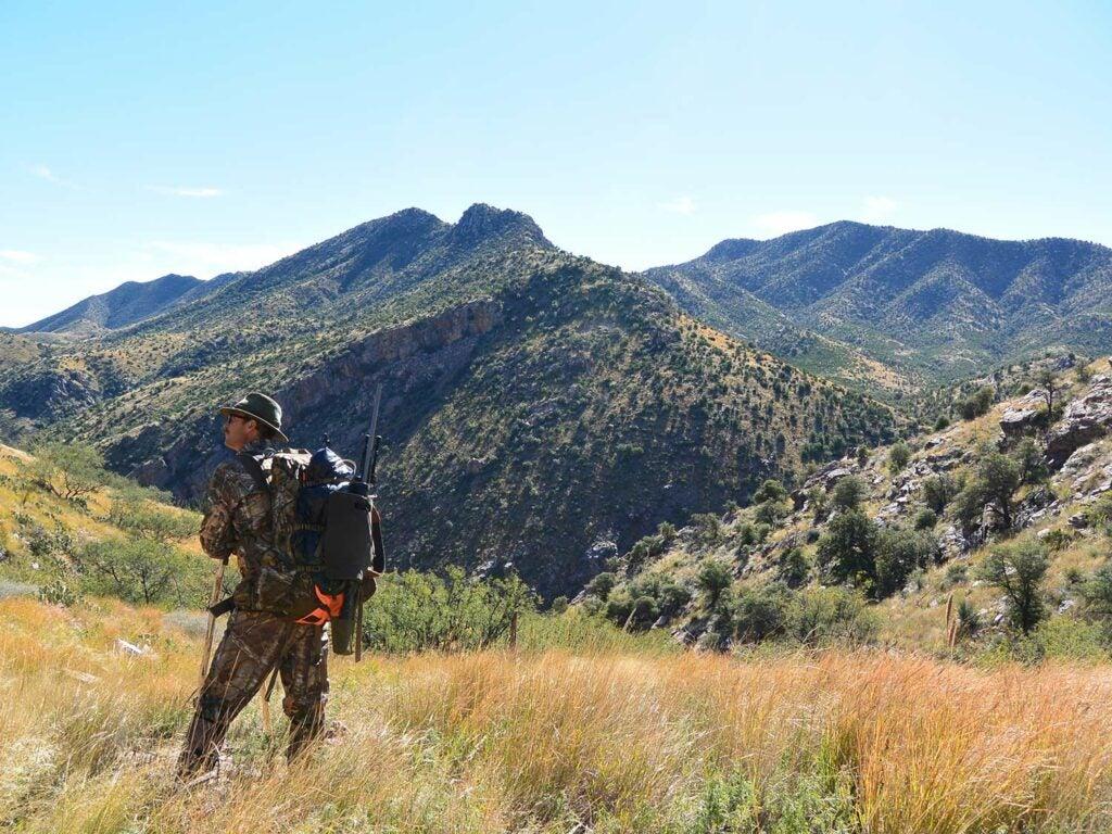 A hunter walks through a large mountainous area.