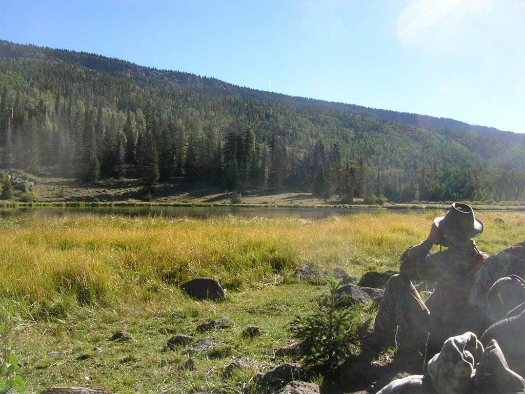A hunter scouts a hillside with binoculars.