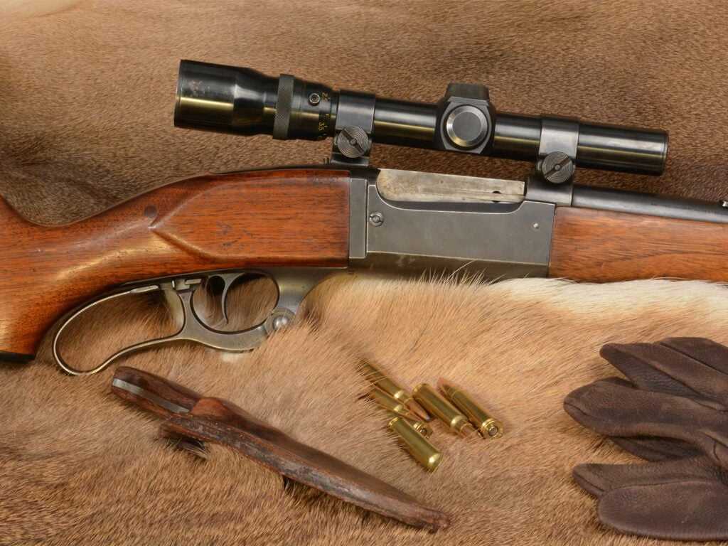 A Savage Model 99 lever action rifle and other hunting gear and bullets on an animal hide.