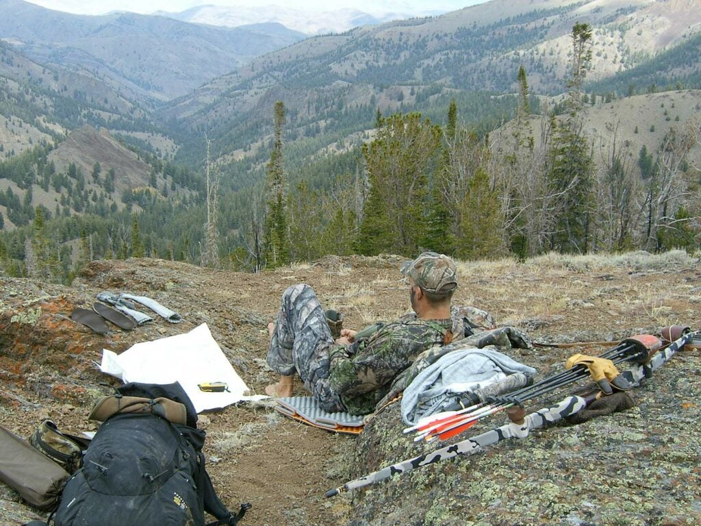 A hunter relaxes at a camp site.