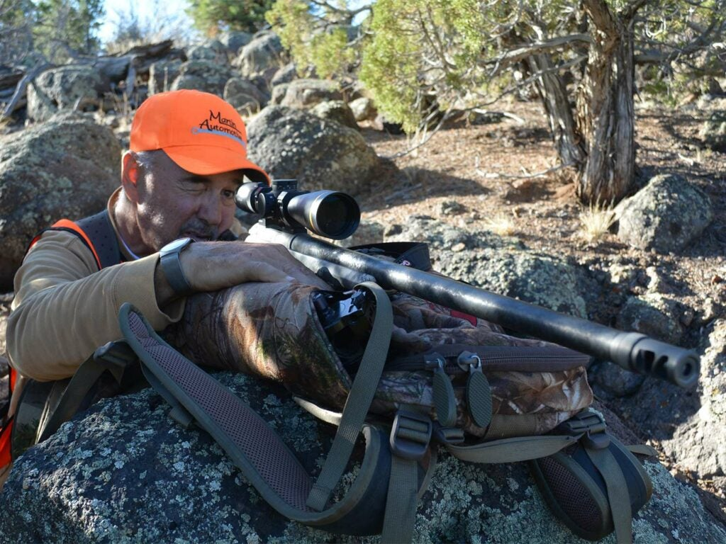 A man aims a rifle in the wilderness.