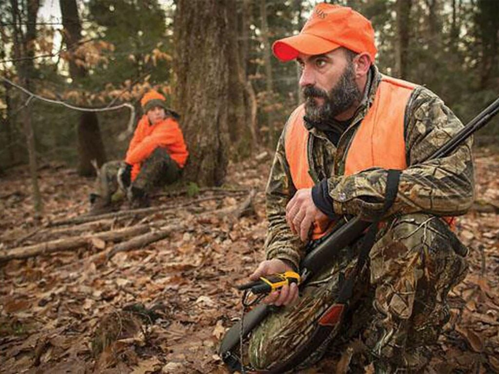 A hunter holds their rifle and crouches in the woods, clutching a 2-way radio in his hand.