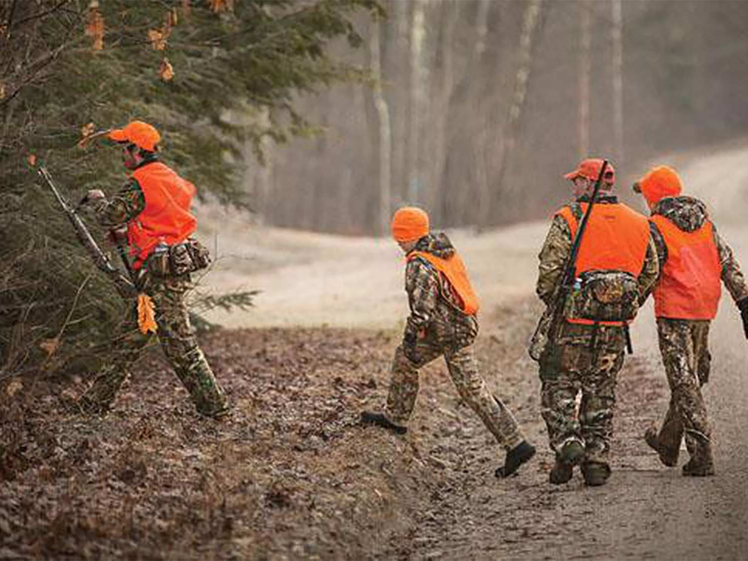 A group of hunters walk through rustling leaves into a tree line.